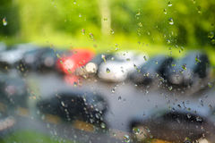 Rain drops on the window. A row of blurry cars outside the window. Summer rain on a sunny day. Rain drops on the window. A row of blurry cars outside the window Stock Photo
