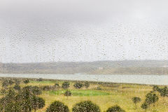 Rain drops on a window. Rain on a window in Spain. The raindrops can be clearly seen. It is still raining and there is cloud. The Guadiana River is in the Stock Photography