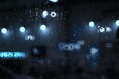 Rain drops on window with street bokeh lights Royalty Free Stock Image