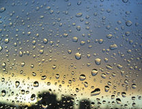 Rain drops on the window, sunset in background, stormy clouds behind #3.  stock photo