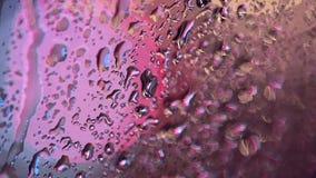 Rain drops on window. Traffic lights bokeh in background, rain running down window. stock footage