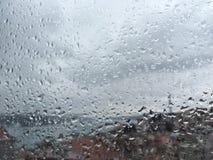 Rain drops on window. Pane against buildings Stock Images