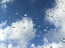 Rain drops on windowpane against clouds Royalty Free Stock Images