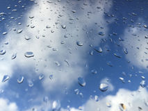 Rain drops on windowpane against clouds Royalty Free Stock Photography