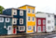 Rain drops on windows with jellybean houses in Newfoundland. Rain drops on windows with jellybean houses in St. John`s, Newfoundland stock photography
