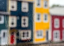 Rain drops on windows with jellybean houses in Newfoundland. Rain drops on windows with jellybean houses in St. John`s, Newfoundland royalty free stock photo