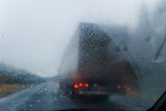 Rain drops on windscreen and blurred truck in forest road. Overtaking of the truck. Low visibility. Stock Photography