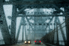 Rain drops on windshield. Wet windshield and blurred traffic during rain storm Royalty Free Stock Images
