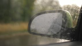 Rain drops on the windshield, on the background side rear view mirror. Rain falling on car glass afternoon car mirror in background. Close up of a car window stock footage