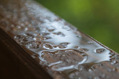 Rain drops on a wooden window sill Royalty Free Stock Photos