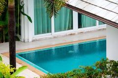 rain fall on swimming pool middle garden in villa stock photos