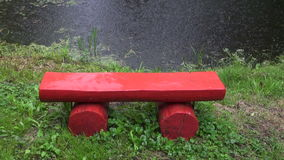 Rain falling on the bench. Rain falling on the red bench standing by the pond in summer stock footage