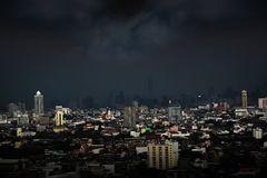 The rain is falling in big city. Gray rain cloud at cityscapes in twilight Stock Image