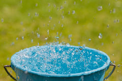 Rain falling into full bucket Stock Image