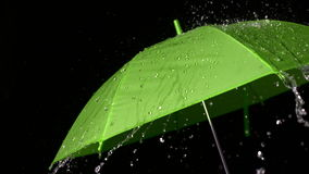Rain falling on green umbrella. In slow motion stock footage