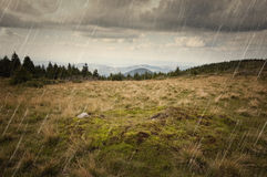 Rain falling over mountain meadow landscape Royalty Free Stock Photography
