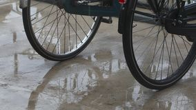 Bicycles in the rain. Rain falling on parked bicycles and pavement stock video footage