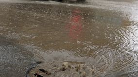Rain falling on road, flowing through sewer drain. Cars drive on a flooded way. Water from heavy rain flows through a manhole cover into a storm drain. Splash stock video footage