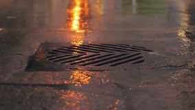 Rain falling in slow motion down a sewer drain at night.