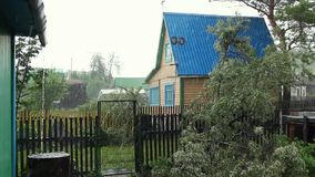 Rain falling on wooden house, downpour in old village, weather. Summer rain in the village, cloudy weather, raindrops falling on the houses stock footage