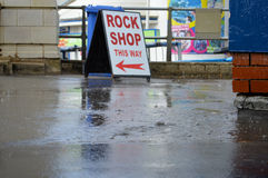 Rain falls into puddles on seaside pier in Bournemouth England. British summer holiday. Detail of rain drops with shop signs and hand railing in background Royalty Free Stock Photos