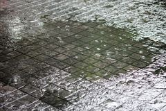 Rain fell heavily, causing flooding at the walkway. The rain fell heavily, causing flooding at the walkway Stock Photos