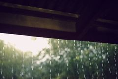 Rain from the roof of the wooden house. The rain fell from the roof of a wooden house in the countryside royalty free stock images