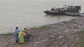 Rain, ferry boat, mekong, cambodia, southeast asia. Southeast Asia, Mekong, Cambodia, Kampong cham,  october 2013. Under rain people getting of board on the stock footage