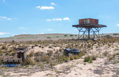 Rain Fill Water Tank. Western Australia farmland with elevated square rusty metal rain fill water tank on wood platform and metal stand with junk piles and sandy Stock Photography