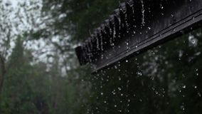 Rain flow from the eaves of a house to the ground stock video footage