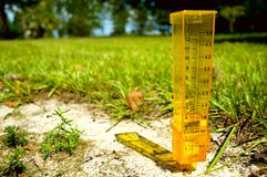 Rain gage. A yellow rain gage with some rain in the sand with a grassy background. Horizontal perspective stock photo