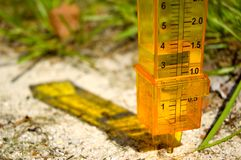 Rain gage. A yellow rain gage with some rain in the sand with a grassy background. Horizontal perspective close view royalty free stock photo