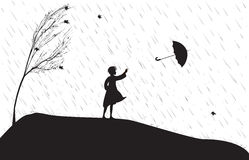 Rain. Girl under the rain trying to catch umbrella, strong wing is blowing, single tree on the heel Royalty Free Stock Image