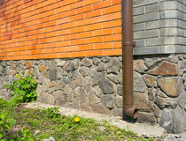 Rain gutter without any drainage systems near house foundation. Royalty Free Stock Images