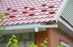 Rain gutter downspout drain pipe installation with metal roof snow board protection. Close up stock image