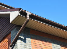 Rain gutter with downspout pipe. Home Guttering, Gutters, Plastic Guttering System. Stock Images