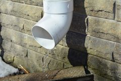 Rain gutter downspout pipe for roof water drainage and waterproofing house foundation wall. Plastic Guttering systems with rain drops water stock image