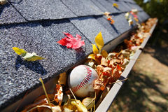 Rain gutter full of autumn leaves with a baseball Royalty Free Stock Photography