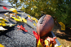 Rain gutter full of autumn leaves with a football Stock Images