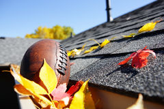 Free Rain Gutter Full Of Autumn Leaves With A Football Stock Photography - 85212512