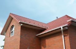 Rain gutter pipe system. Close up on attic brick house with clay roof tiles and plastic roof gutter pipes drain. Guttering royalty free stock images