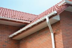 Rain gutter pipe system. Close up on Brick house with roof tiles and plastic roof gutter pipes drain. Guttering. Roofing royalty free stock image