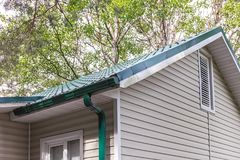 Rain gutter system and tiled roof against green trees stock photo