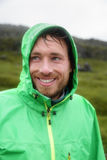Rain jacket - man smiling outdoors on rainy day royalty free stock photography