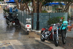 After rain. Motorcycles parked near glass enclosures outdoor cafes on the shore of lake Voulismeni in Agios Nikolaos after rain. Crete, Greece stock photo
