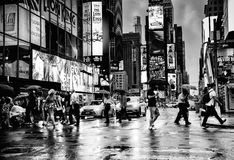 People in intersection of Times Square, New York City. People with umbrellas crossing busy intersection in Times Square in New York City at night in the rain in stock photos