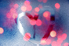 Rain at night, draw heart shape on wet glass with light Royalty Free Stock Photo