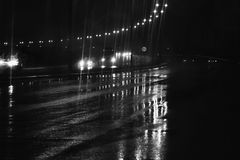 Rain at night on the road with street lights in the dark street. Rain at night on the road with street lights in monochrome , Black and White photo B&W. The dark Royalty Free Stock Photography