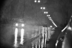 Rain at night on the road with street lights in the dark street. Rain at night on the road with street lights in monochrome , Black and White photo B&W. The dark Stock Photo