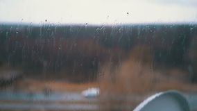Rain outside the window. Raindrops flow down the glass. Bad, depressive weather. Autumn or spring stock footage
